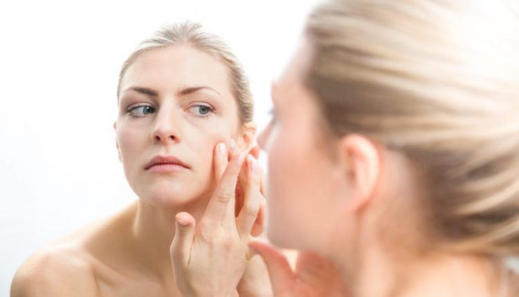Young bare shouldered woman checking pimples